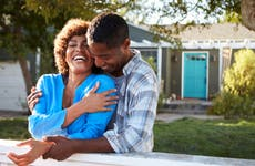 Mature couple laughing in front of house