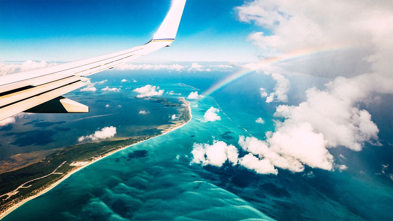Plane over an island with a rainbow