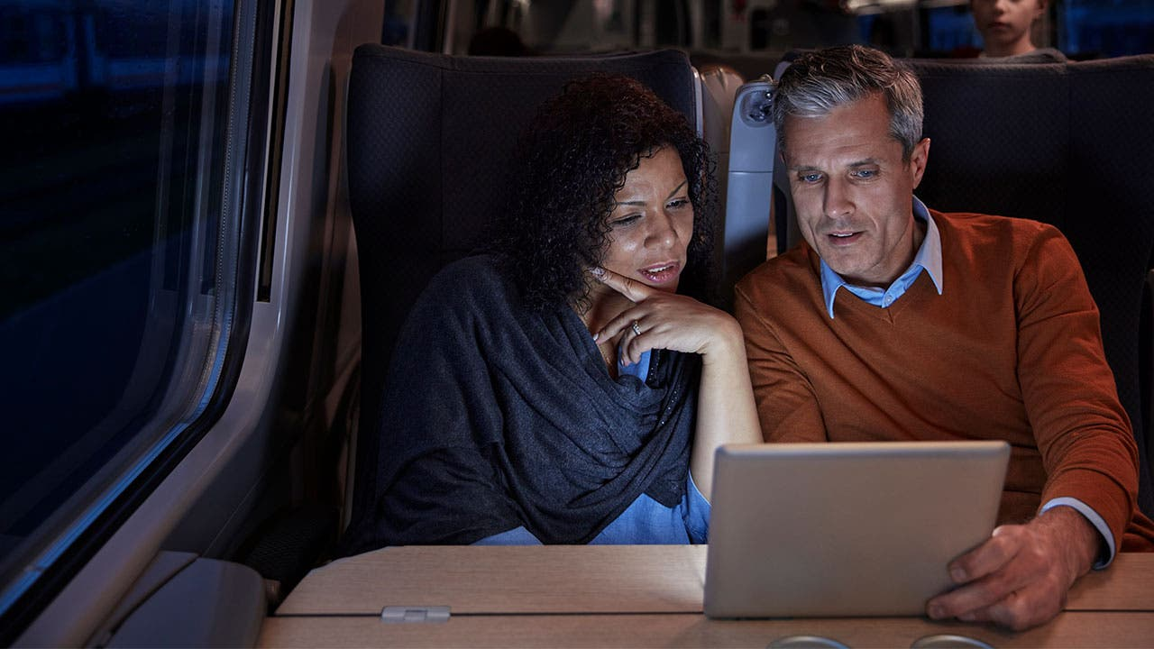 Couple on train looking at tablet