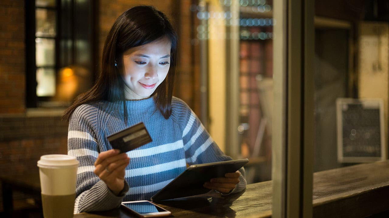 Woman paying with credit card on tablet