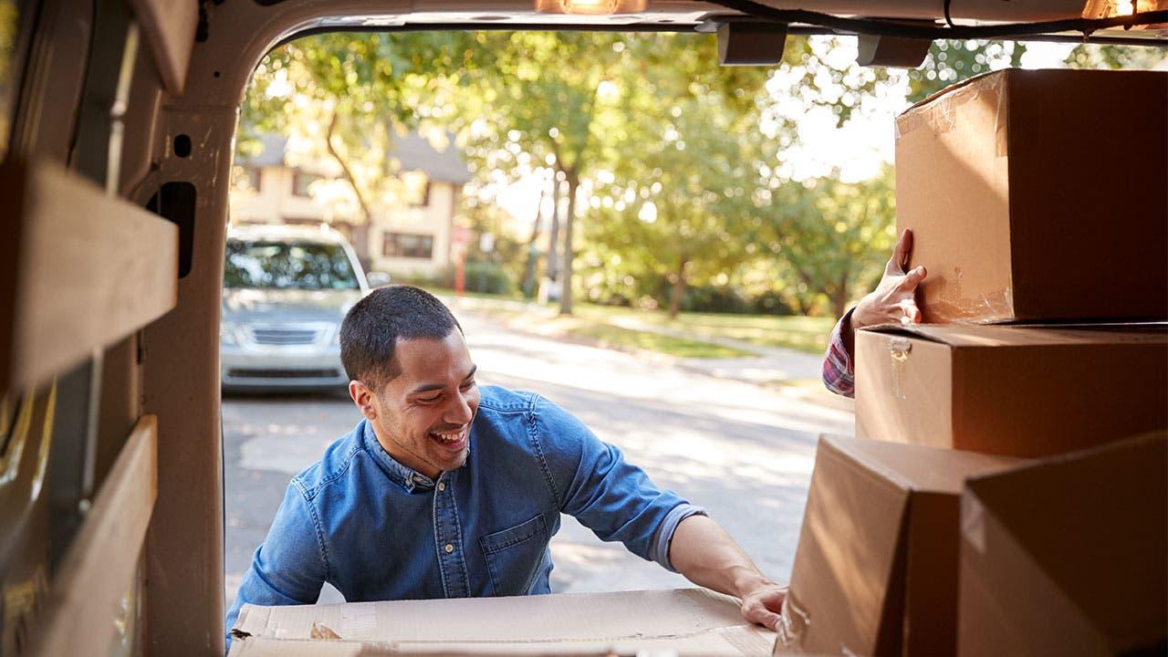 Man boxing boxes in van