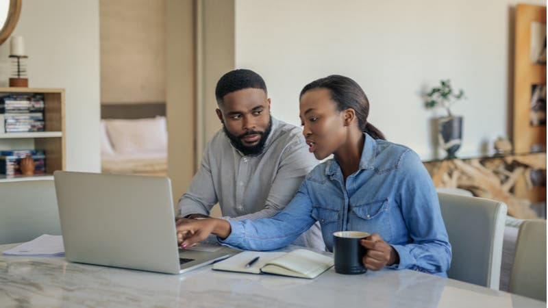 Young couple doing taxes on a laptop
