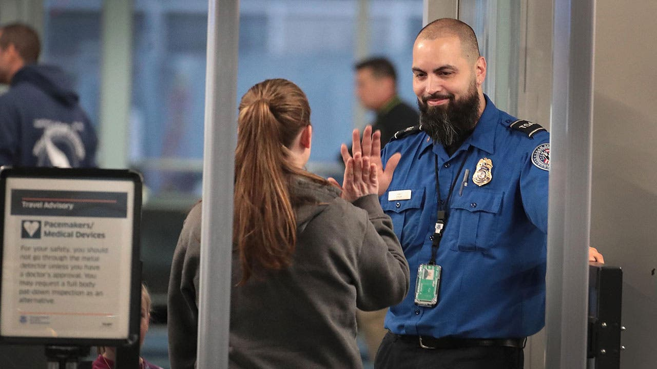 TSA worker high fives traveller
