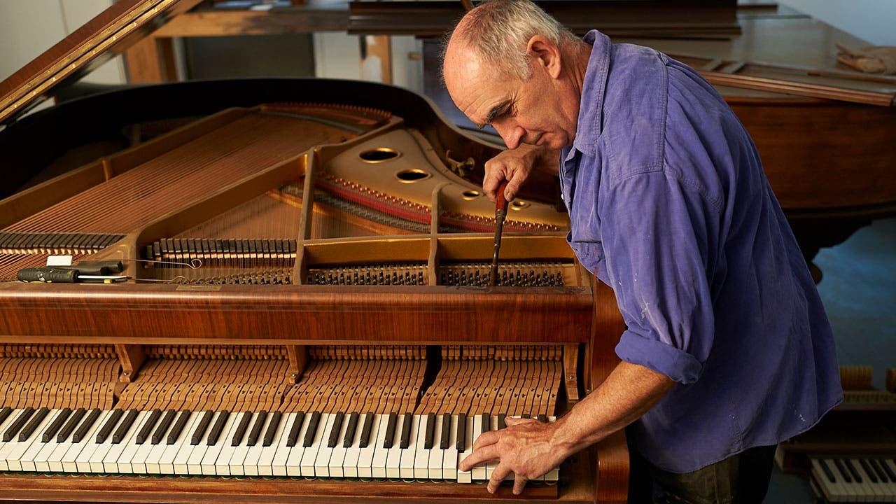 Man tuning piano