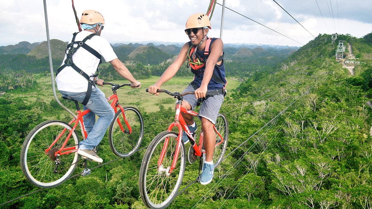 Two men biking on ziplines