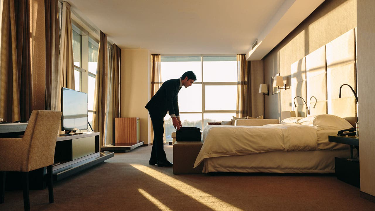 Man opening suitcase in hotel room