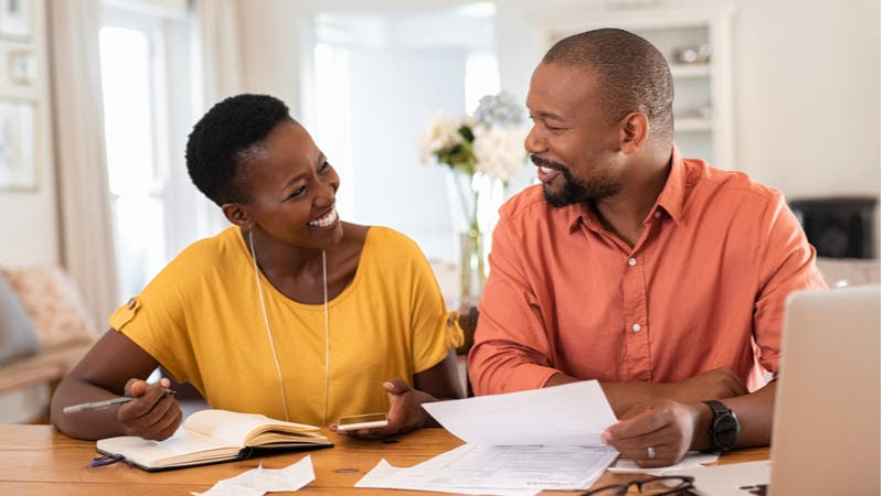Middle aged couple review finance paperwork together
