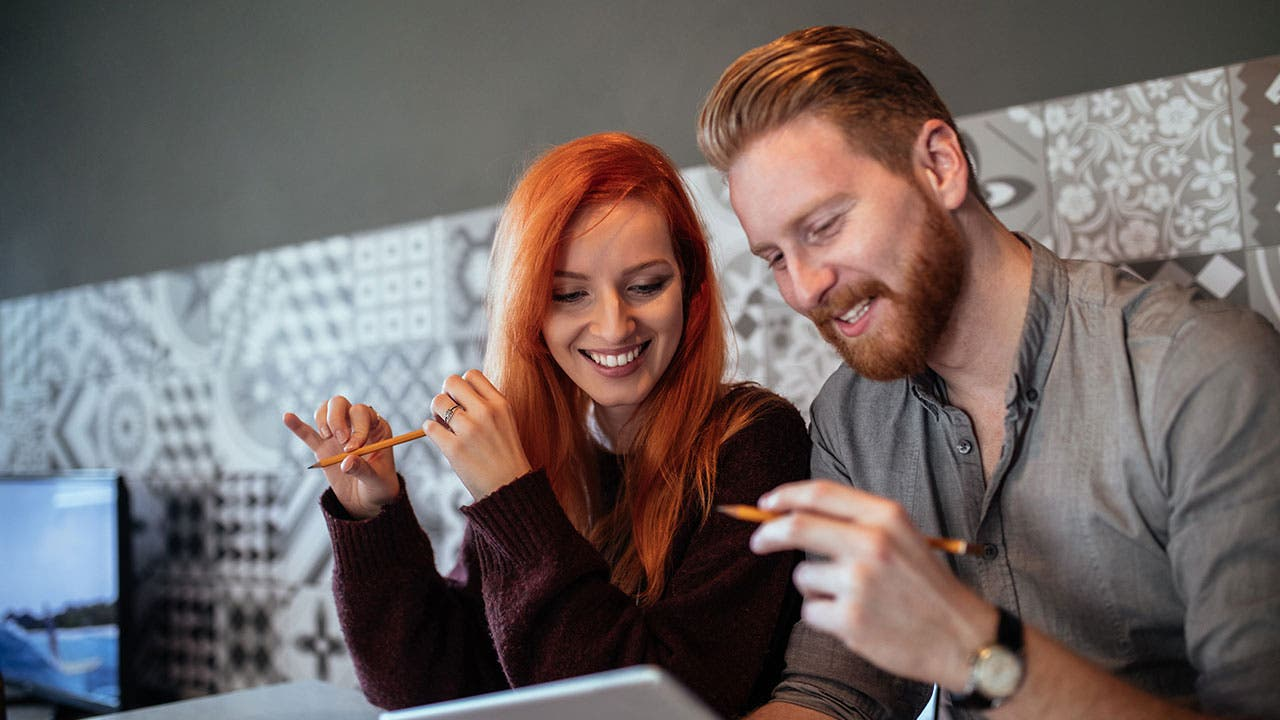 Couple looking at paying debts on tablet