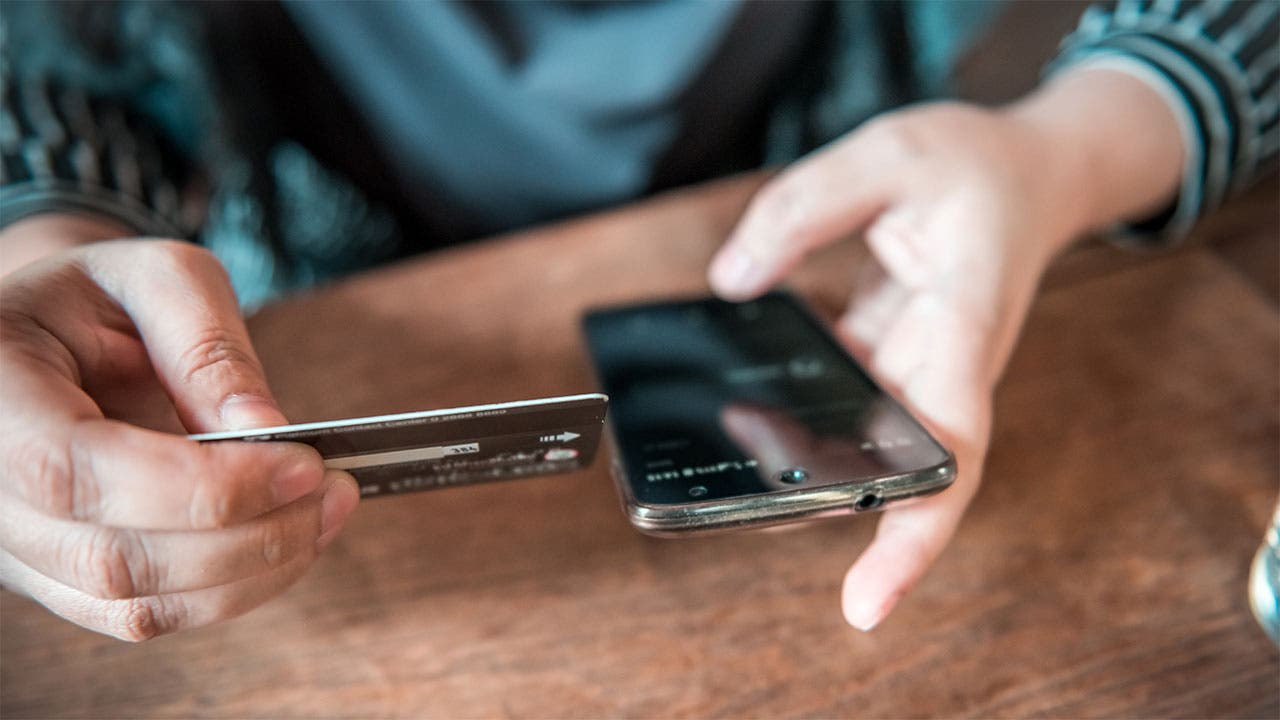 Man looking at phone to pay credit card which reached its credit card limit