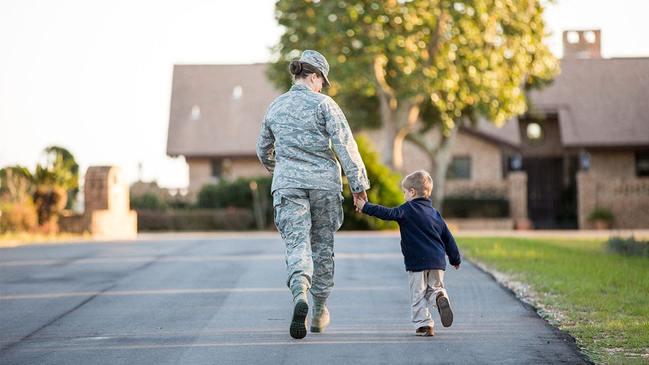 Military member walking with child