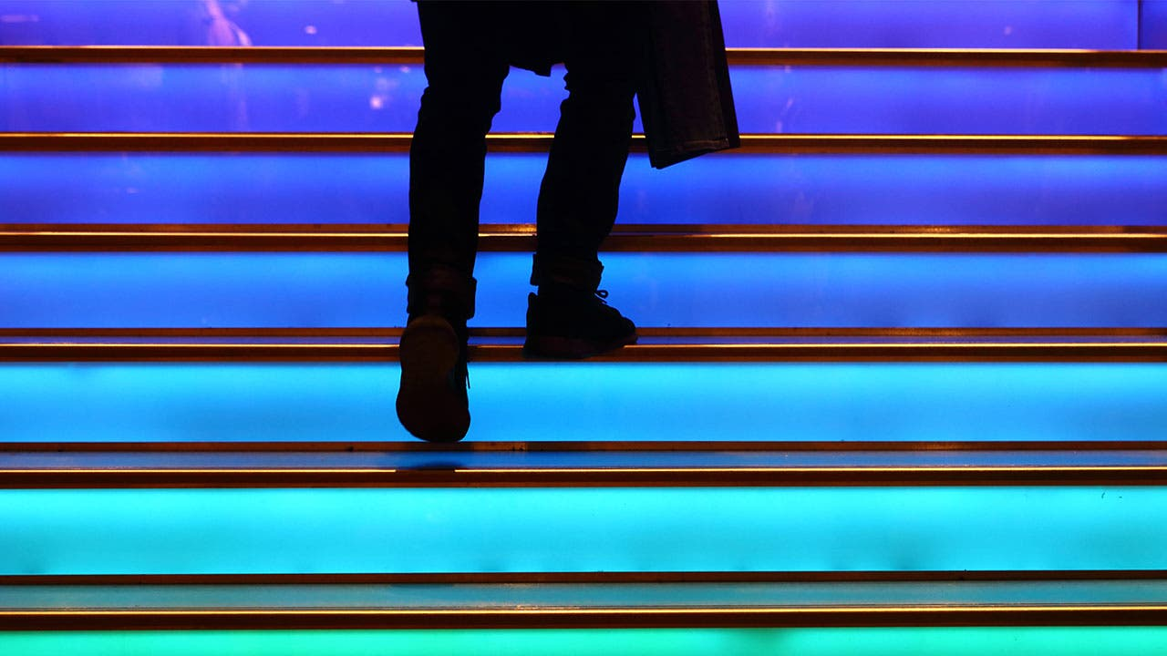 Man walking up the colored stairs