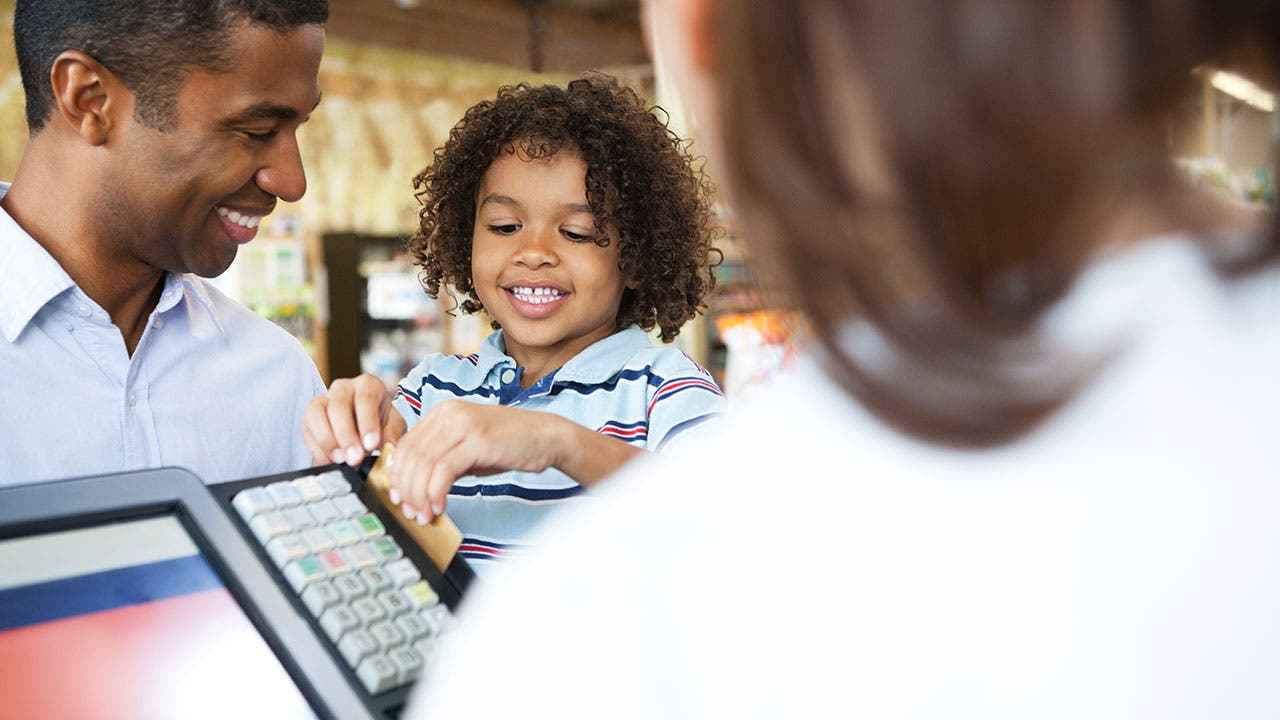 Child paying with a credit card at store