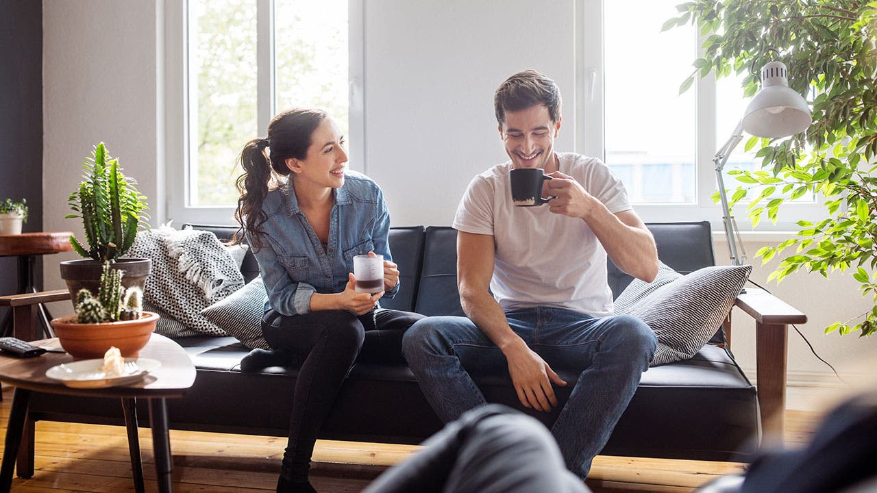 Couple drinking coffee in livingroom
