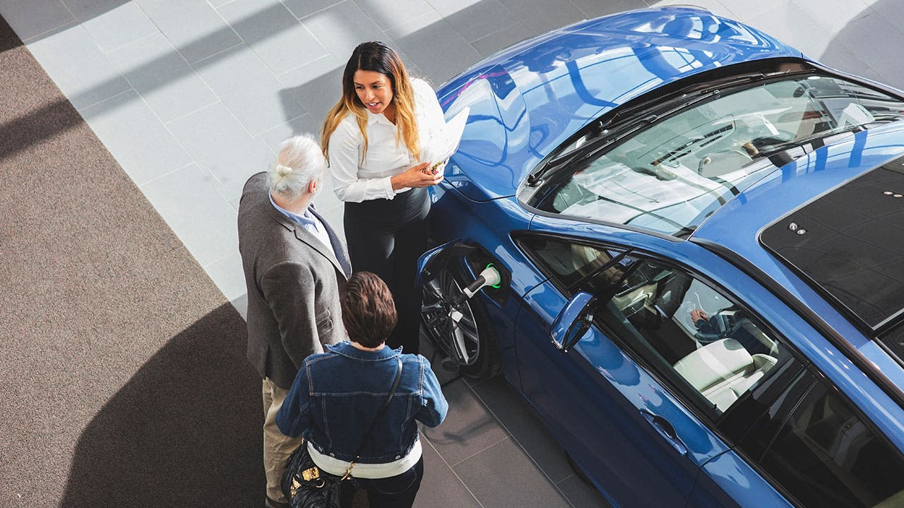 Couple buying at car at a dealership