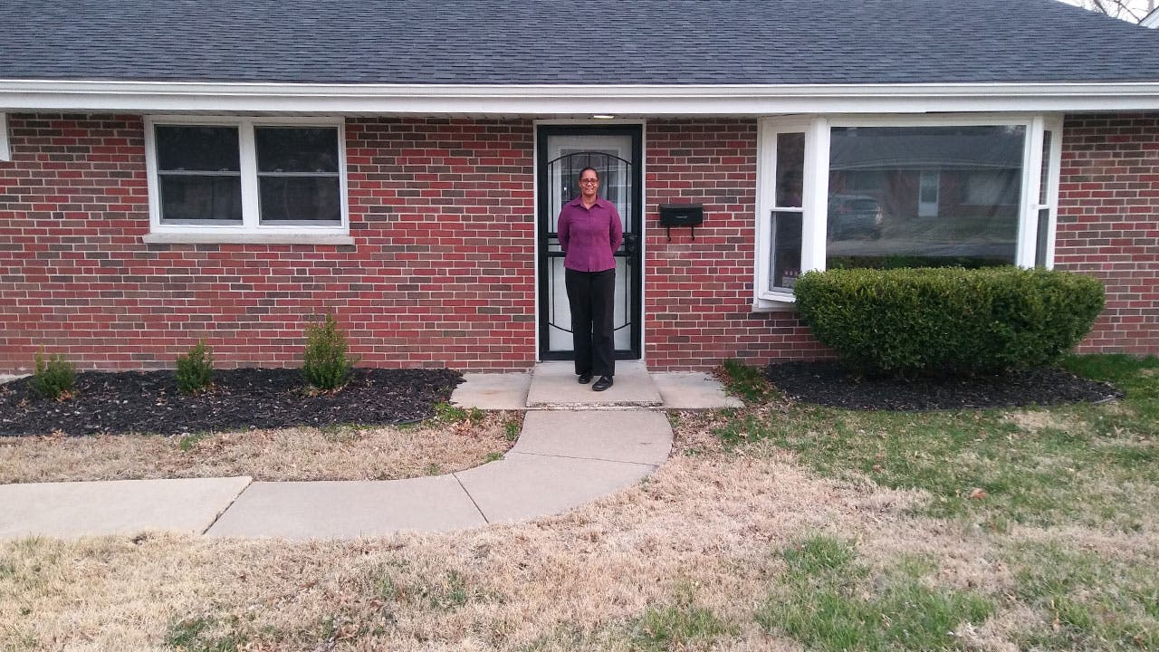 Sharon Townsend in front of her home