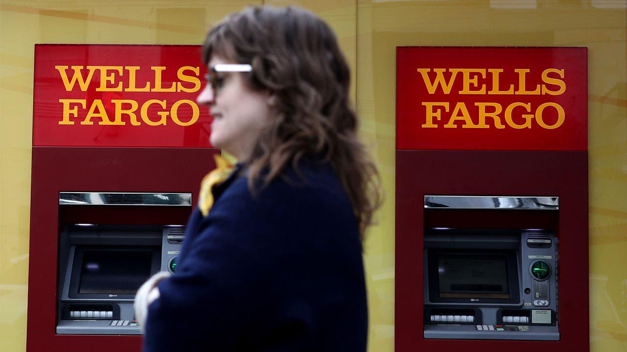 Woman walking past Wells Fargo atm