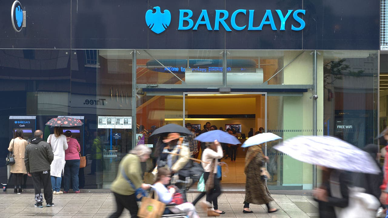 People walking past Barclays bank