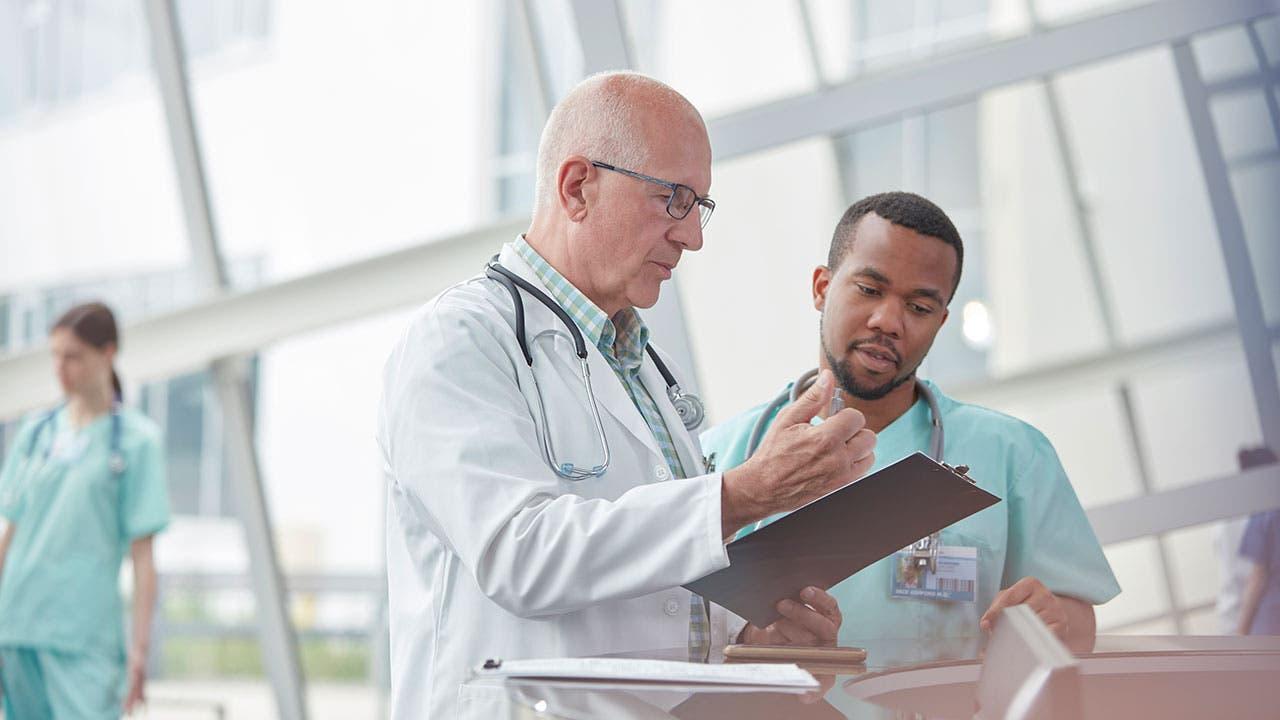 Older doctor talking with nurse