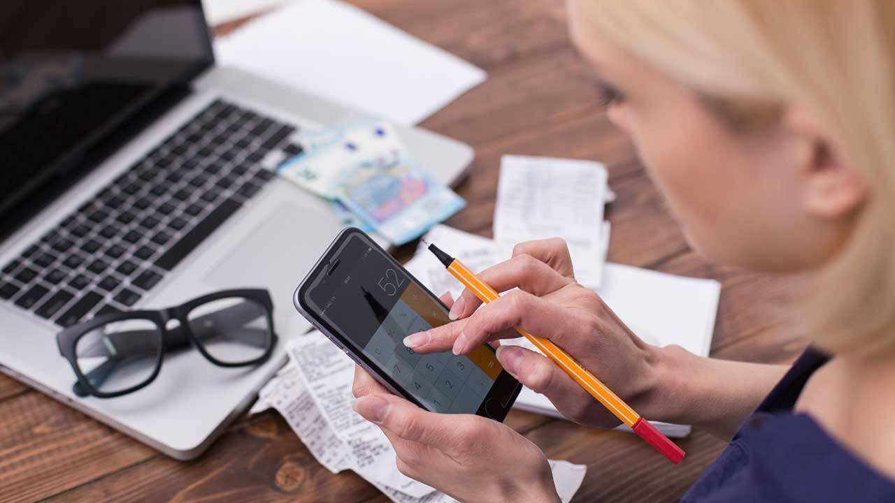 Woman checking receipts and using mobile calculator
