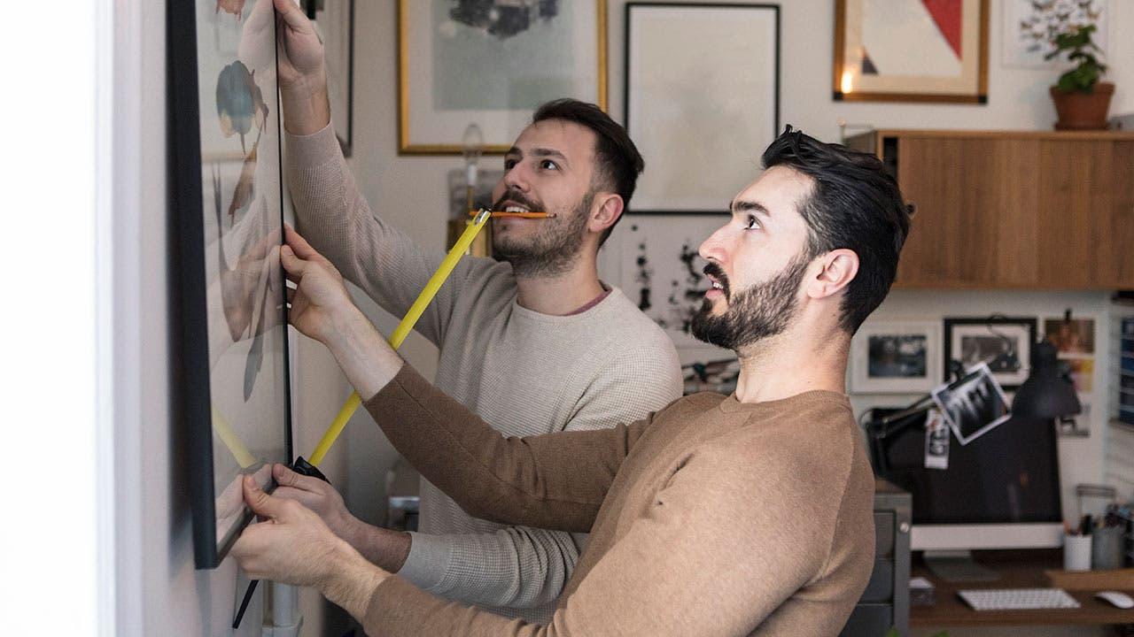 Men hanging art in home