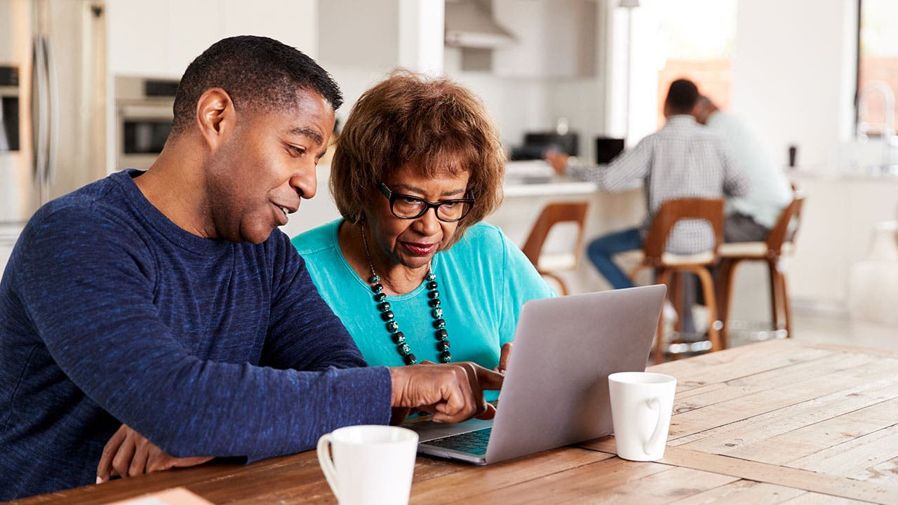 Son showing mother how to online bank