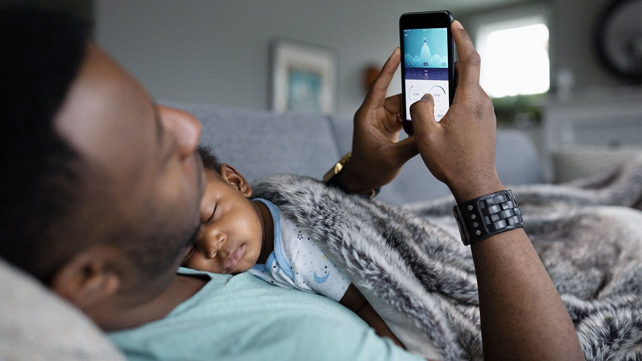 Father looking at phone while his son sleeps