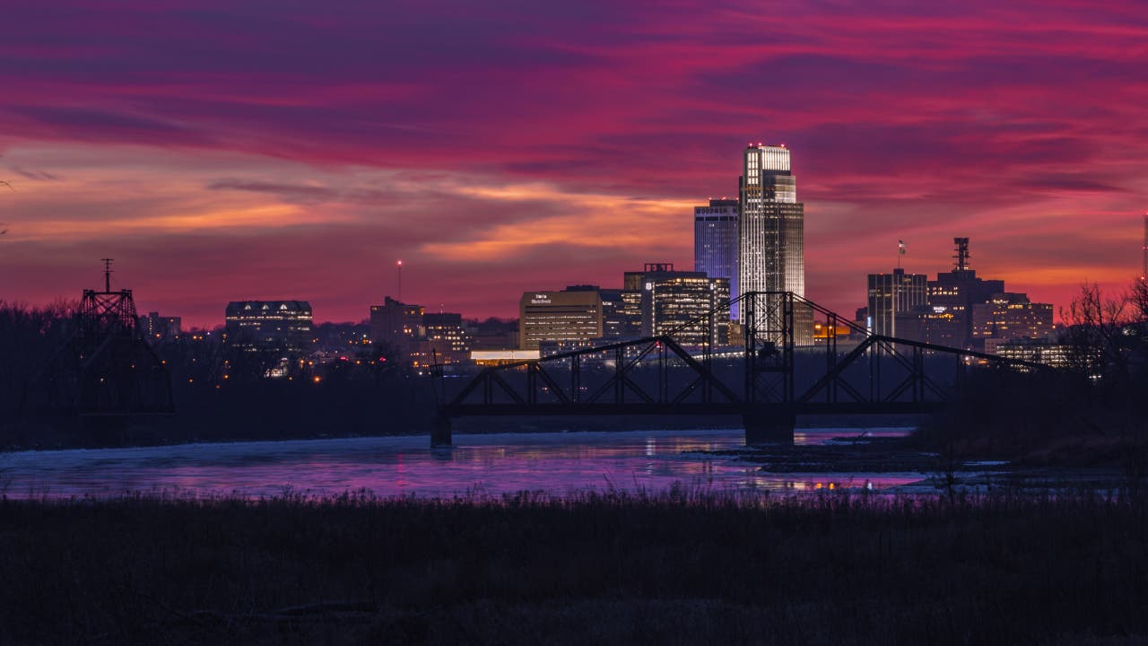 Illuminated buildings by a river in Omaha, Nebraska during sunset.