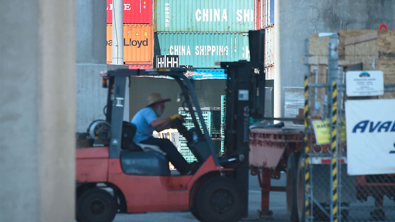Man using a forklife to move Chinese containers