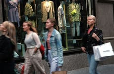 Shoppers walk down the street with shopping bags