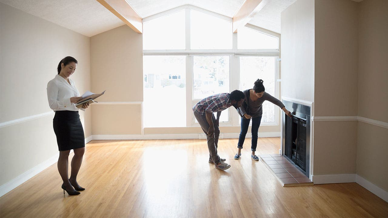 Couple inspecting a fireplace in a home walk through