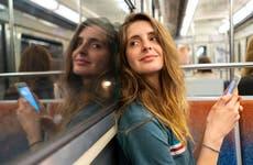 Man sits on a subway train texting