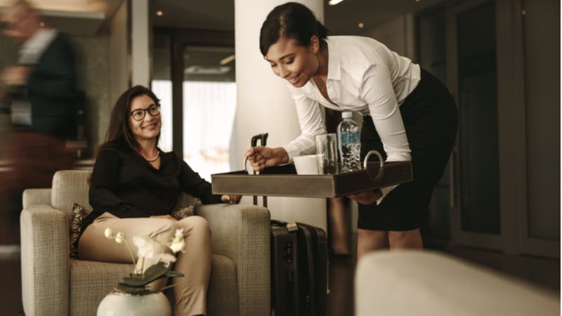 Businesswoman getting served a beverage in airport lounge