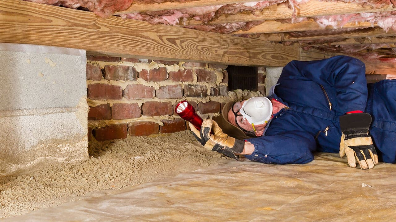 Home inspector looking under insulation