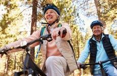 Couples rides bike through forrest