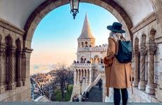Woman looking out over steps of historic building in Budapest