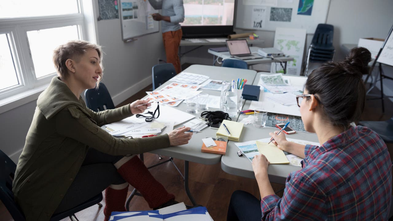 Two women sitting at a cluttered office table working
