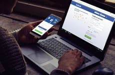 A person holds a smartphone and laptop with Facebook open