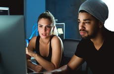 man and woman look at computer screen, worried