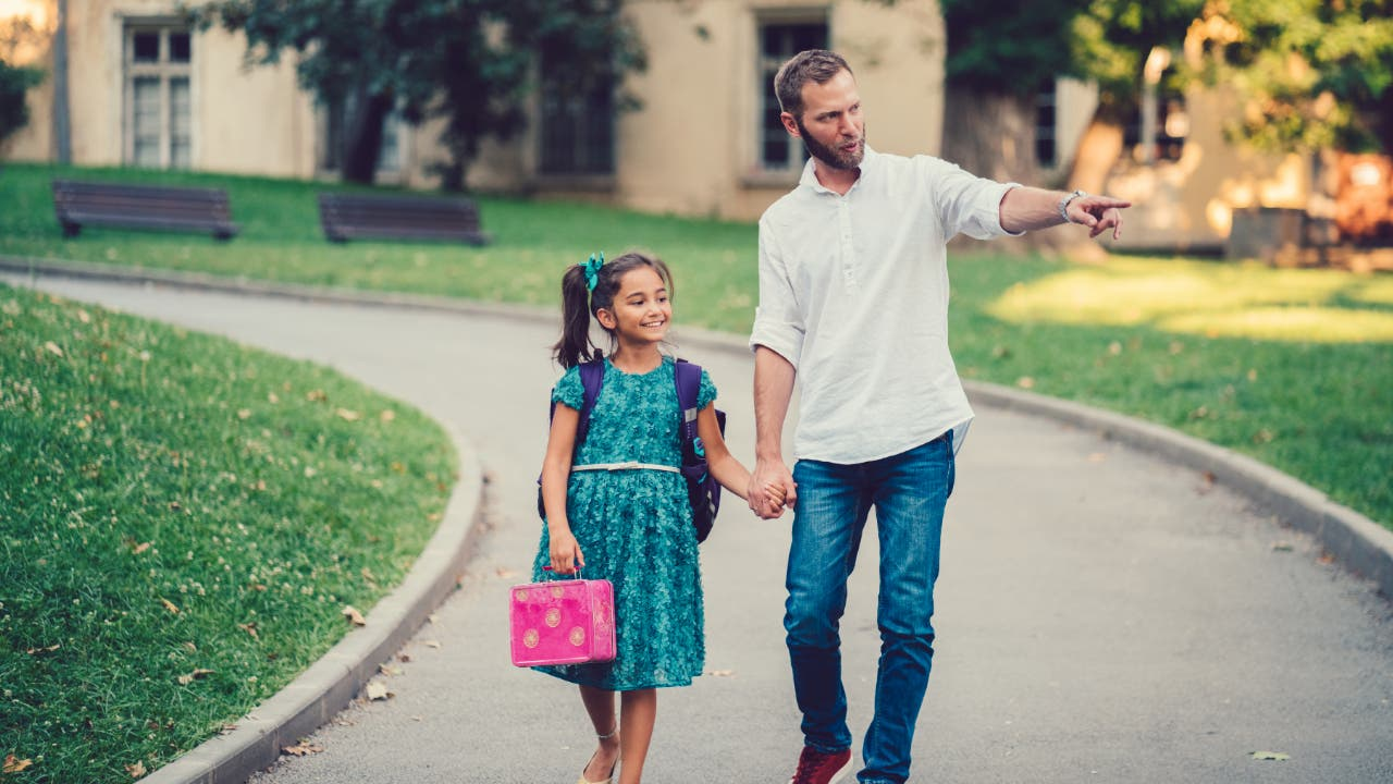 Father walking his daughter to school