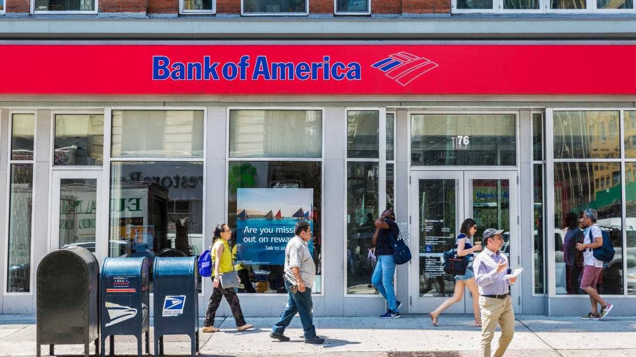 People walking by a Bank of America storefront.