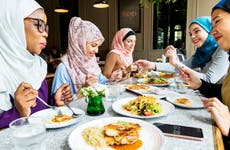 Group of young muslim women enjoying a meal at a restaurant