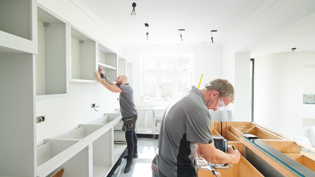 Cabinet installers working in a kitchen