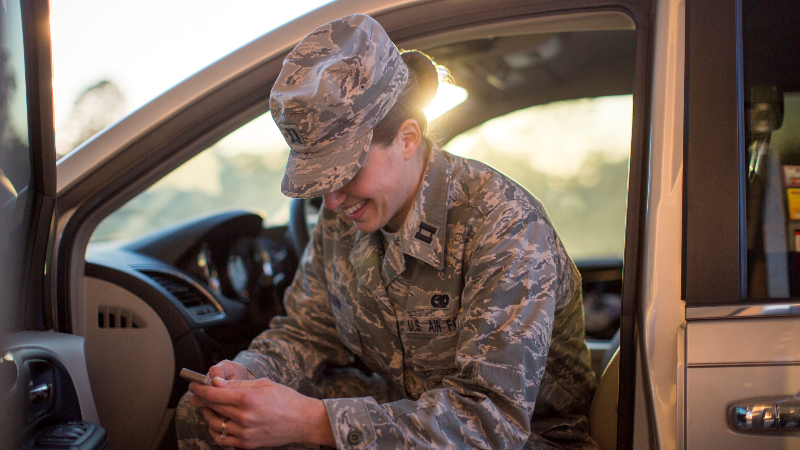 female soldier texting in car