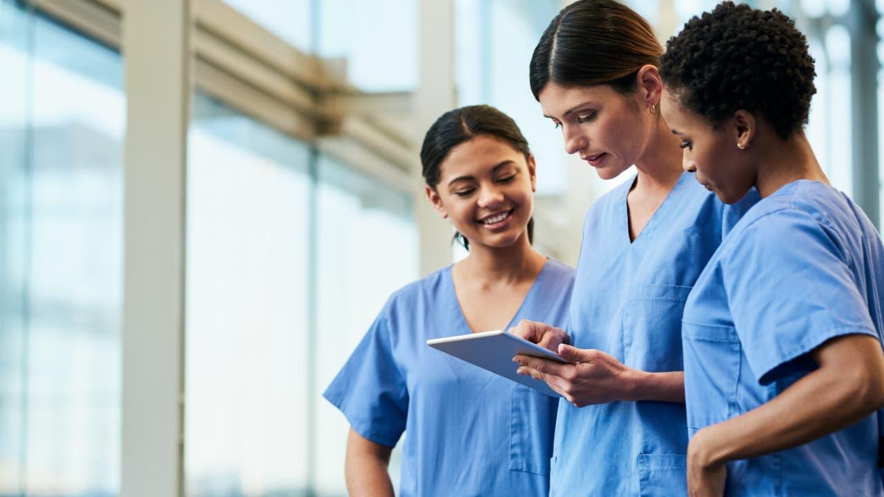 3 nurses looking at iPad