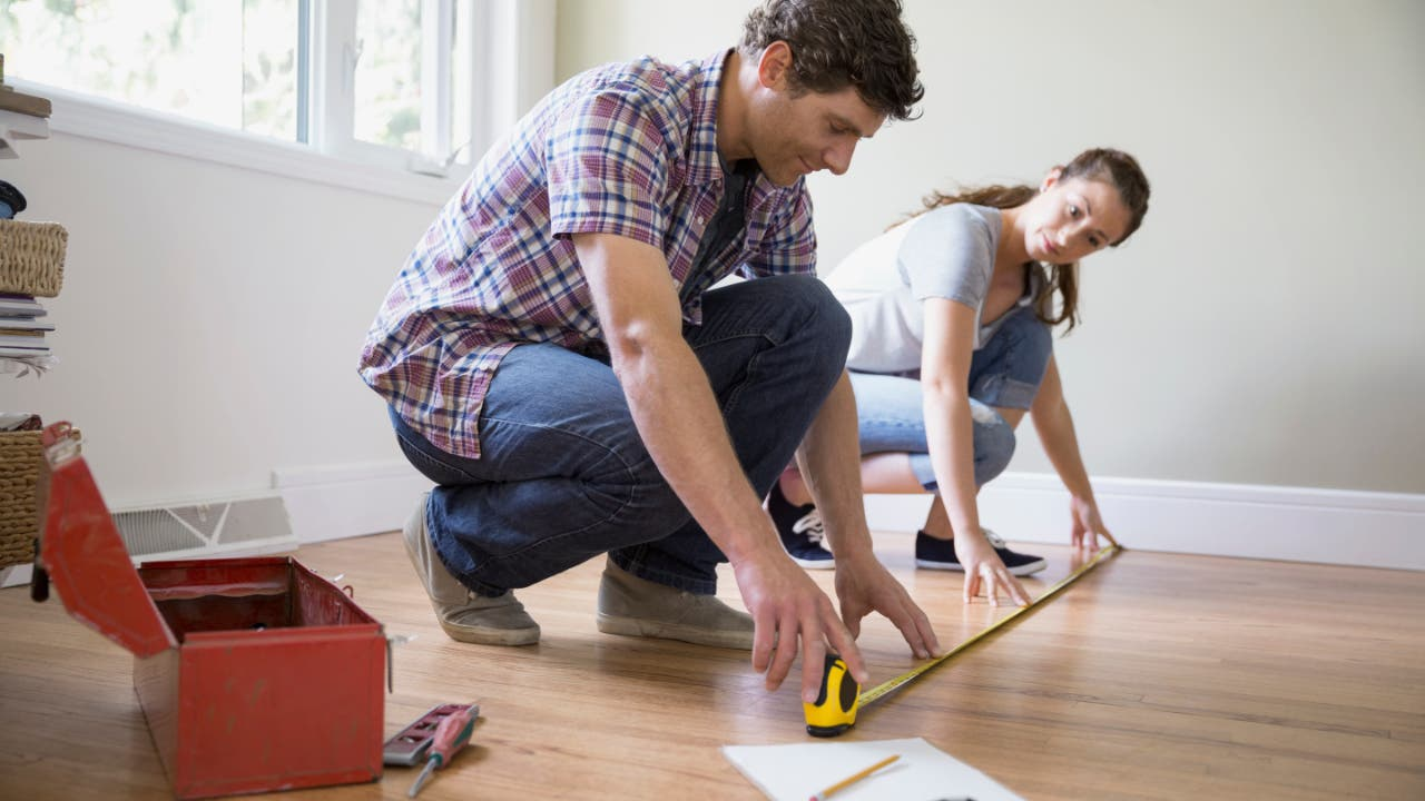 Couple measuring a hardwood floor