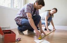 Couple measuring a hardwood floor
