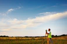 A land surveyor conducts a land survey