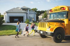 Children getting off a school bus to go home.