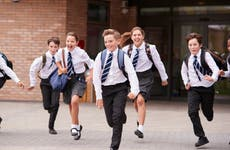 A group of private school children in uniform dashes in front of a school