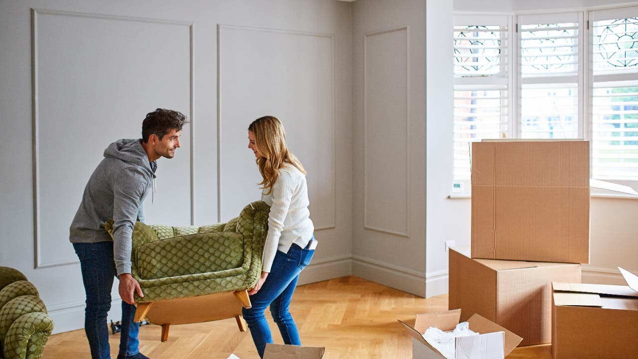 A couple moving furniture into a house.